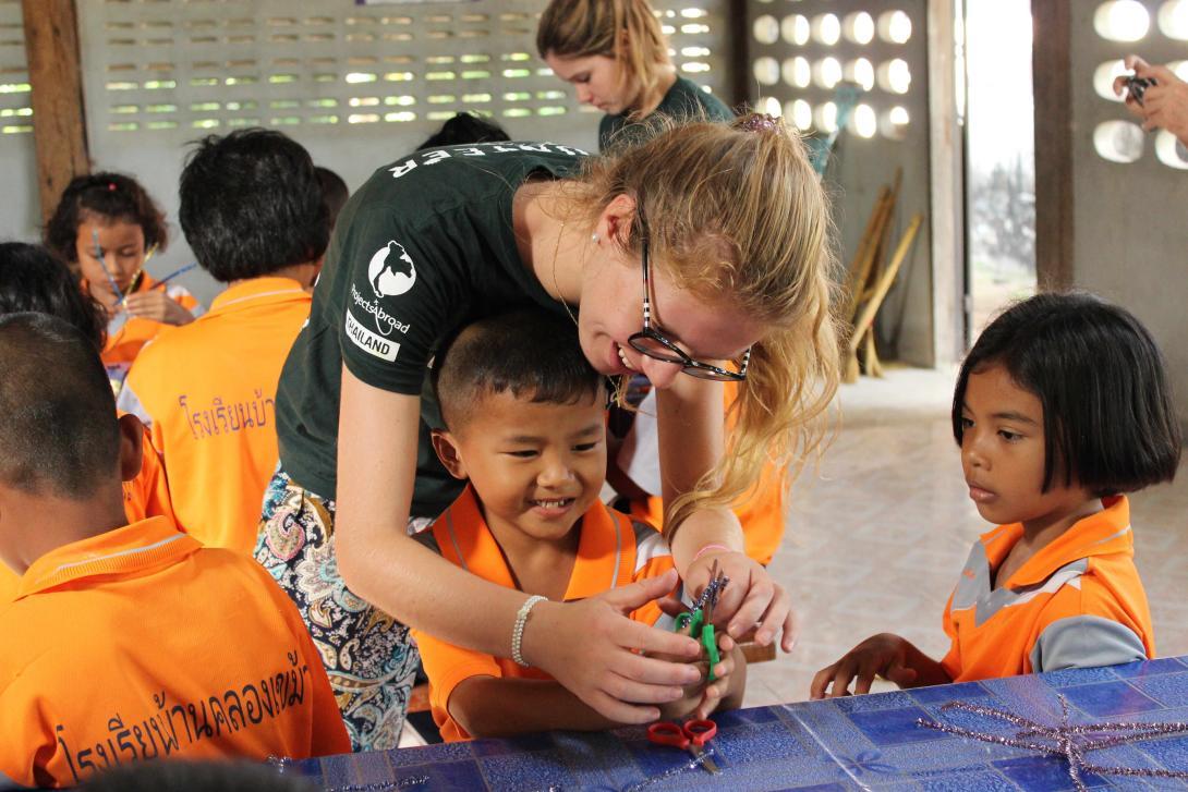 En un viaje solidario, una voluntaria de Educación en Tailandia ayuda a los niños en una lección de arte.
